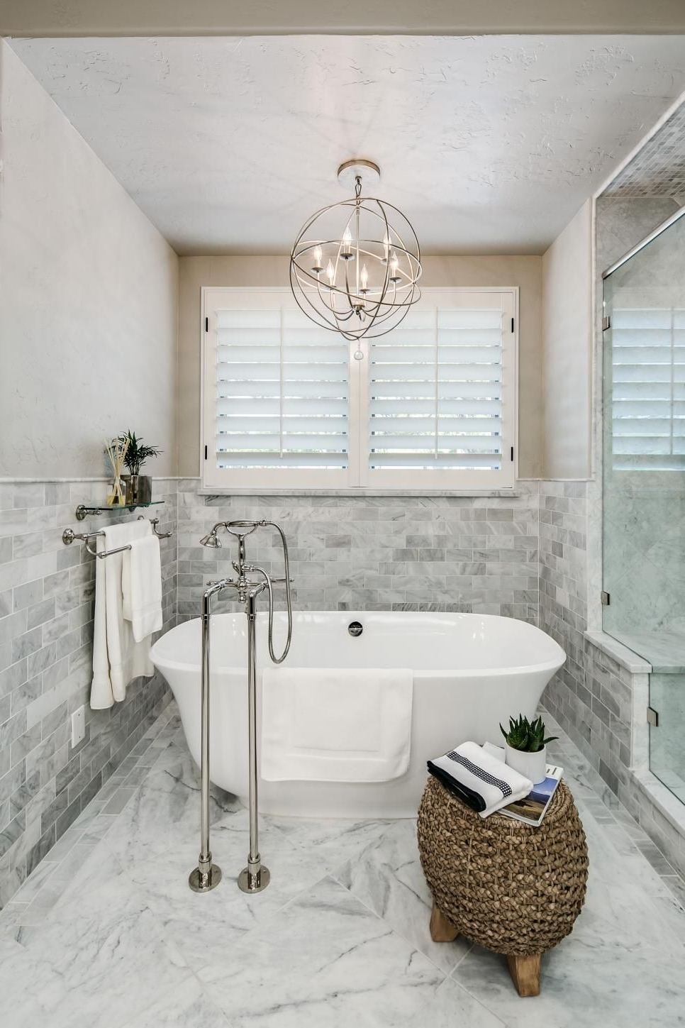 Latest Chandeliers For Bathrooms Pertaining To A Metal Orb Chandelier Is Centered Above The Freestanding Tub In (View 7 of 15)