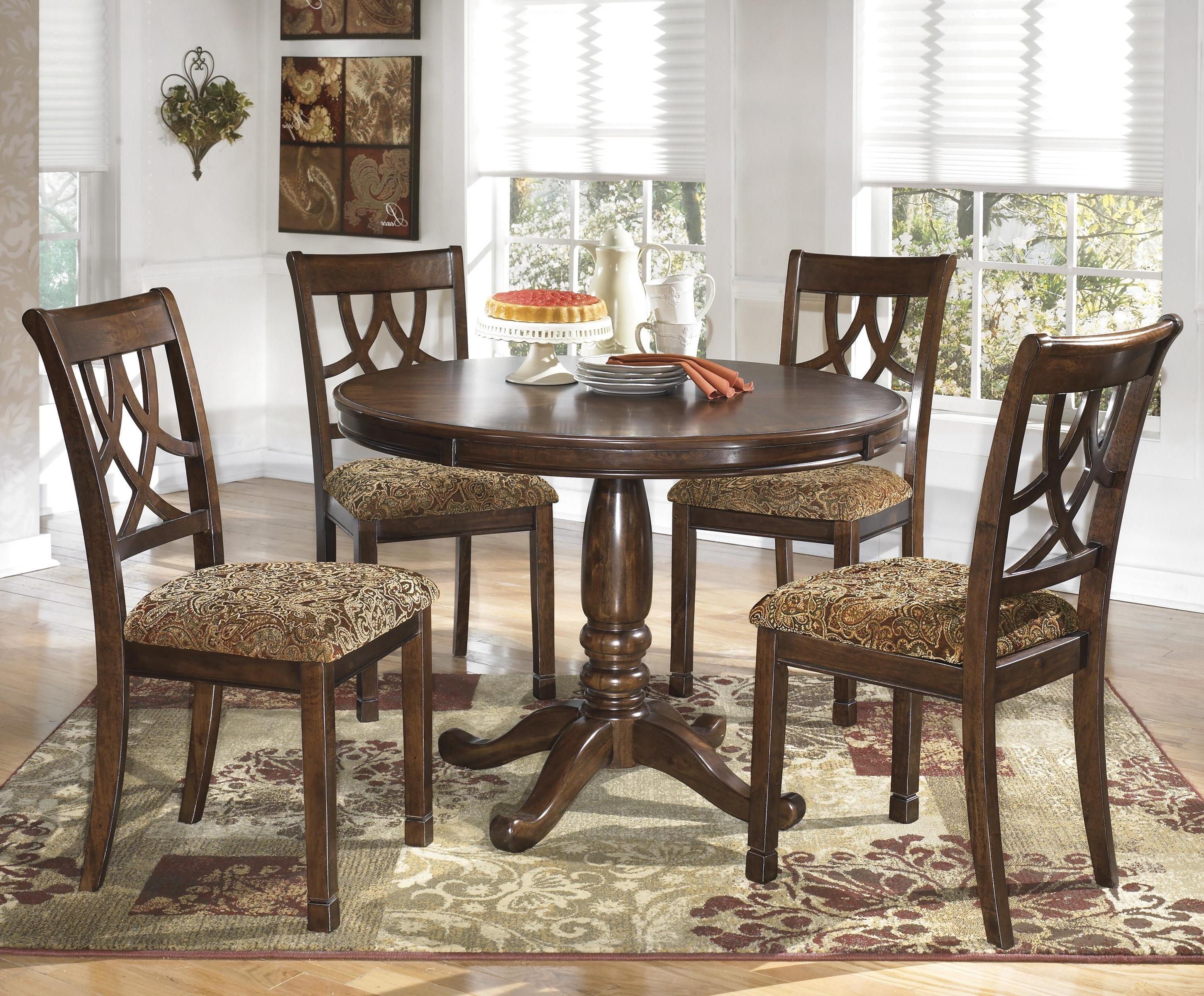 Signature Designashley Leahlyn 5 Piece Cherry Finish Round With Regard To Fashionable Jaxon 5 Piece Round Dining Sets With Upholstered Chairs (View 20 of 25)