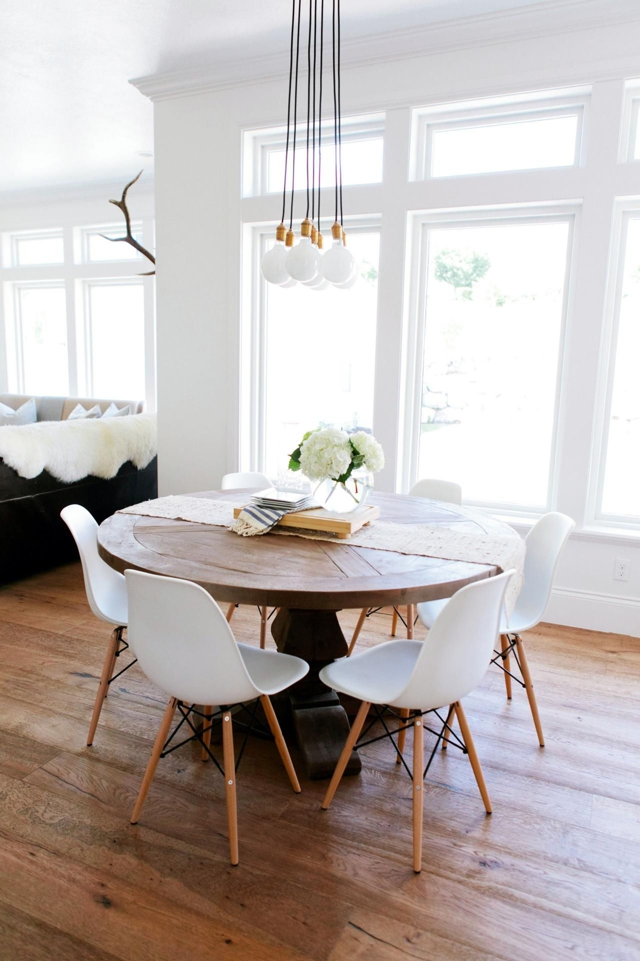 White Dining Chairs In Well Liked A Rustic Round Wood Table Surroundedwhite Eames Dining Chairs (View 24 of 25)